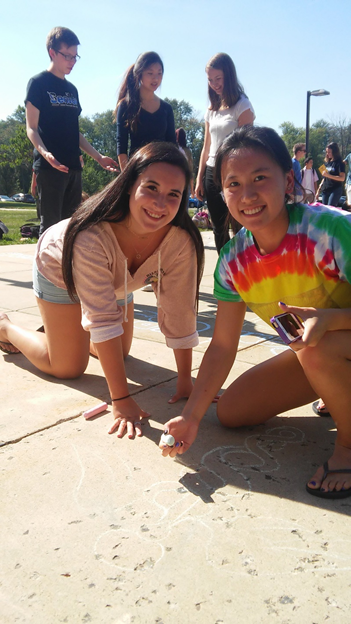 Nina Disandro (left) and Emily Cid (right) are working together to draw the medical symbol for the HOSA square.