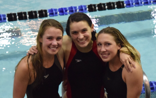 Lauren McCarthy (left) with her teammates, Shannon Murphy (center) and Sam Mrozinski (right), at a swim meet. Photo from Lauren McCarthy.